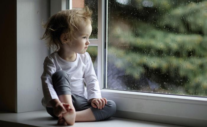 copil la geam, privind ploaia